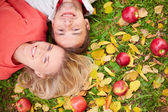 Couple lying on ground with red apples — Stock Photo