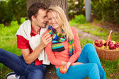 Young couple sitting in park — Stock Photo