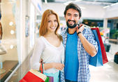 Couple with paperbags in mall — Stock Photo