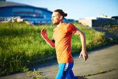 Sportsman with earphones running — Stock Photo