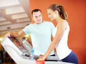Girl in gym with her trainer — Stock Photo