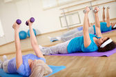 Females doing exercise with barbells — Stock Photo