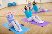 Females doing physical exercise — Stock Photo