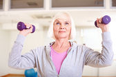 Woman doing exercise with barbells — Stock Photo