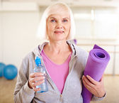 Woman with bottle of water and rug — Stockfoto