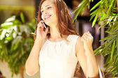 Girl talking on the phone in mall — Stock Photo