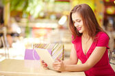 Girl using touchpad after shopping — Stock Photo