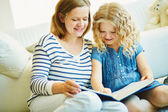 Girl and her mother reading a book — Stock Photo