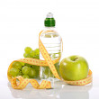 Bottle with aqua, apple grapes, and measure - Stock Photo
