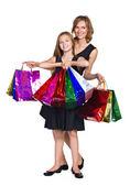 Matka a dcera v elegantních šatech s mnoha barevnými tašky — Stock fotografie
