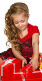Beautiful little girl looking box set with presents — Stock Photo