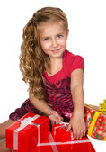 Beautiful little girl sitting with presents in a box set — Stock Photo