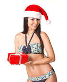 Beautiful young woman in swimsuit and Santa Claus hat with prese — Stock Photo