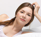 Beautiful young woman in a bed — Stock Photo
