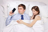Businessman and woman in bed — Stock Photo