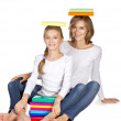 Mother and daughter sitting on the floor with books on heard — Stock Photo #27256253