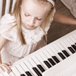 Stock Photo: Little girl playing on piano