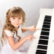 Stock Photo: Little girl and piano