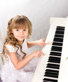 Little girl and piano — Stock Photo