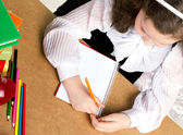 Little schoolgirl writing — Stock Photo