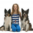 Young girl sitting between two Border Collies against white background — Stock Photo