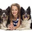 Stock Photo: Young girl lying between two Border Collies against white background