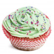 Stock Photo: Cupcake with green icing and hundreds and thousands against white background in front of white background