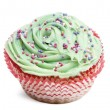 Cupcake with green icing and hundreds and thousands against white background in front of white background - Stock Photo