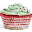 Cupcake with green icing and hundreds and thousands against white background in front of white background - Foto Stock