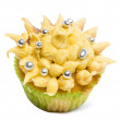 Cupcake with yellow icing and decoration against white background in front of white background - Stock Photo