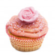 Cupcake with pink flower decoration against white background in front of white background - Stockfoto
