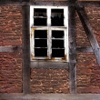 Stock Photo: Old broken window in wall of old house