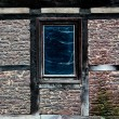 Stock Photo: Old window in web in wall of old house