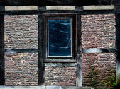 Old window in a web in the wall of old house — Stock Photo