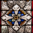 Fragment of colored ornamental glass of window of the church - Stock Photo