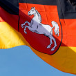 Stock Photo: German flag of Lower Saxony against blue sky