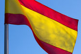 Spaanse vlag op de achtergrond van de blauwe hemel — Stockfoto