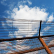 Royalty-Free Stock Photo: Security fence against the blue sky