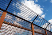 Security fence against blue sky — Stock Photo