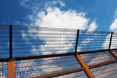 Security fence against the blue sky — Stock Photo