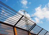 Barrier fence and Electricity pylon against the sky — Stock Photo