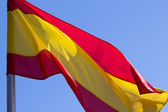 Spanish flag on a background of blue sky — Stock Photo