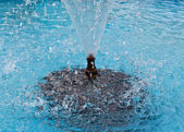 Water spray of fountain on the turquoise background — Stock Photo