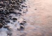 Sea shore in the light of rising sun — Stock Photo