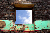 Old wall of house ruins and window against sky — Stock Photo