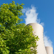 Green tree branches against a nuclear power plant — Stock Photo