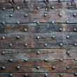 Old, brown wooden surface with metal knobs — Stock Photo