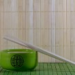 Green teapot and chopsticks against straw mat — Stock Photo #39386725