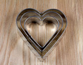 Heart shape cookie molds on wooden surface — Stock Photo