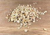 Oat flakes on wooden surface — Stock Photo